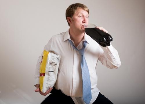 お菓子を持ってコーラを飲もうとする外国人サラリーマン